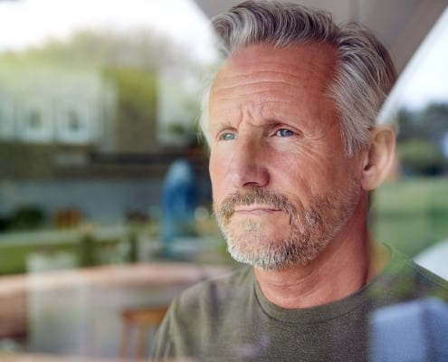 Man looking out window with worried look on his face